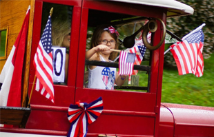 girl waving flag from vintage car during fourth of july festivities