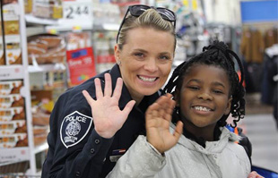 a staunton police officer and child wave at the camera during the shop with a cop event