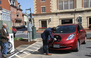 a man charges a Nissan Leaf demonstrating the electric car charger