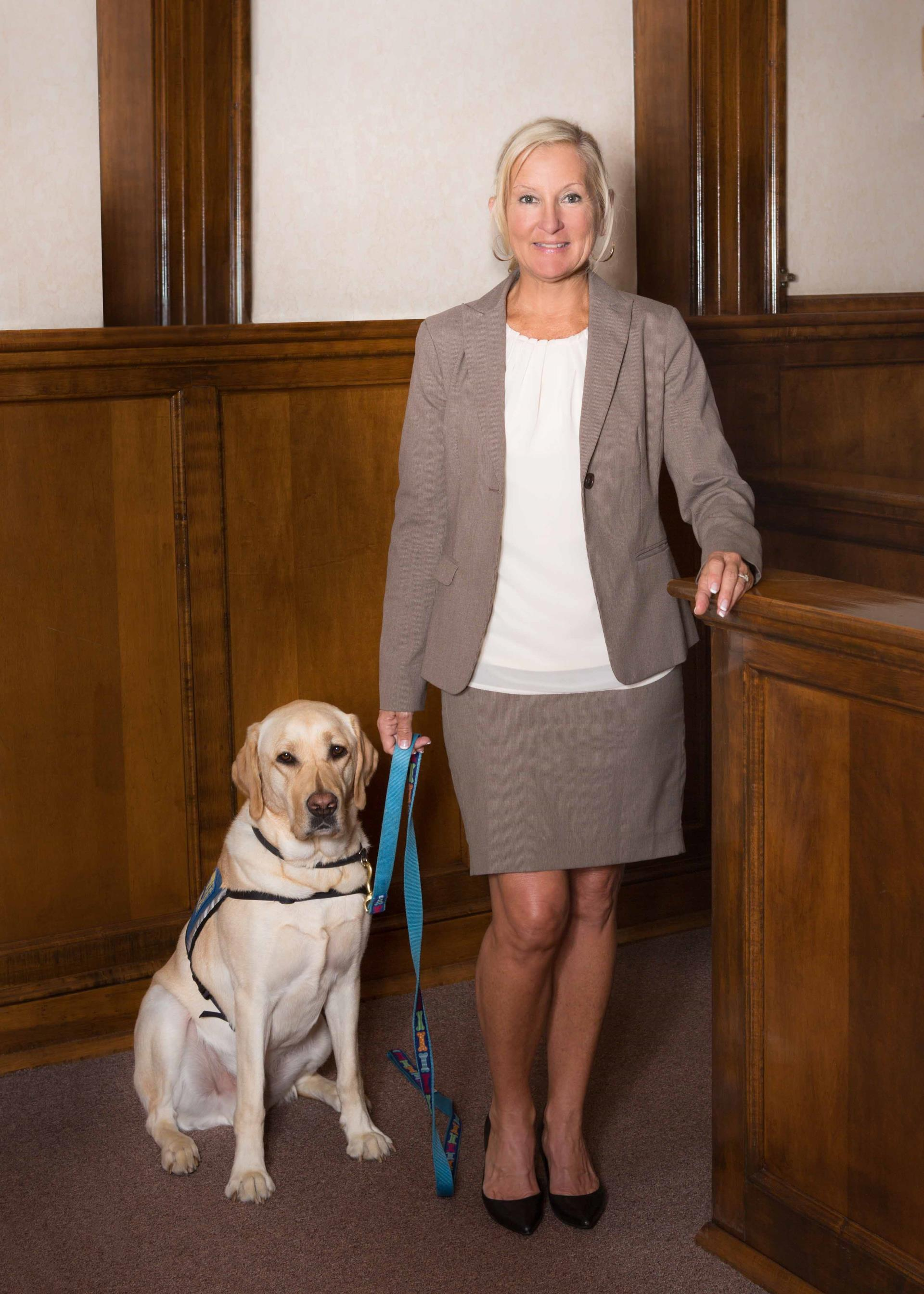 Murph, the courthouse facility dog for the victim-witness program, accompanied by Janet Balser, his handler