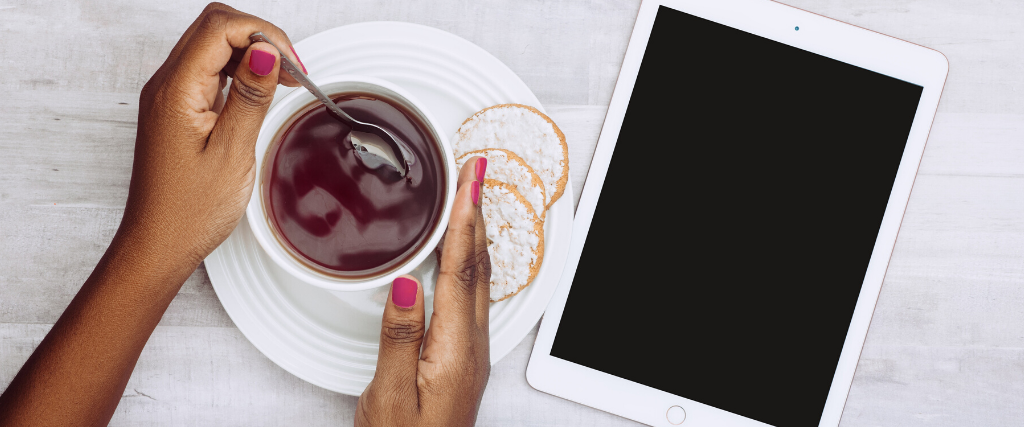 Hands holding a coffee cup with an iPad next to the saucer.